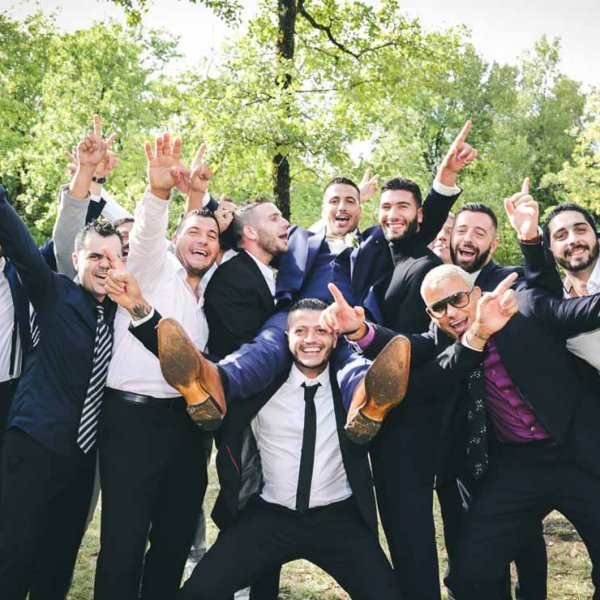 photos des amis qui porte le marié pendant la fête de la cérémonie
