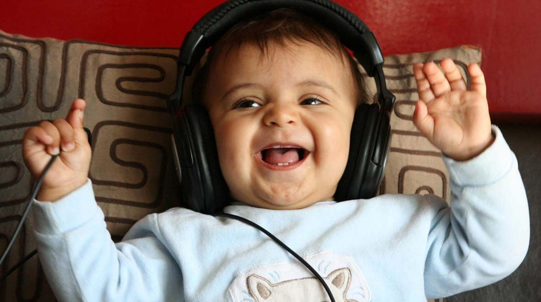 Photo professionnel de bébé en train de rire avec un casque sur les oreilles