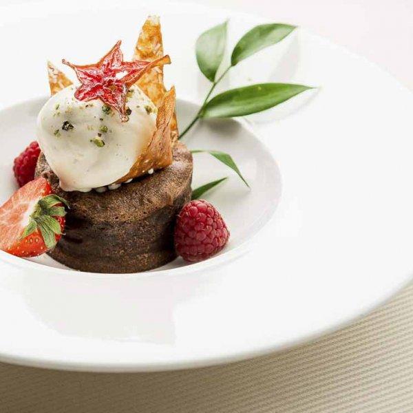 Photographe professionnel culinaire plat d'un restaurant en dessert chocolat fondant avec fraises et glace à la vanille