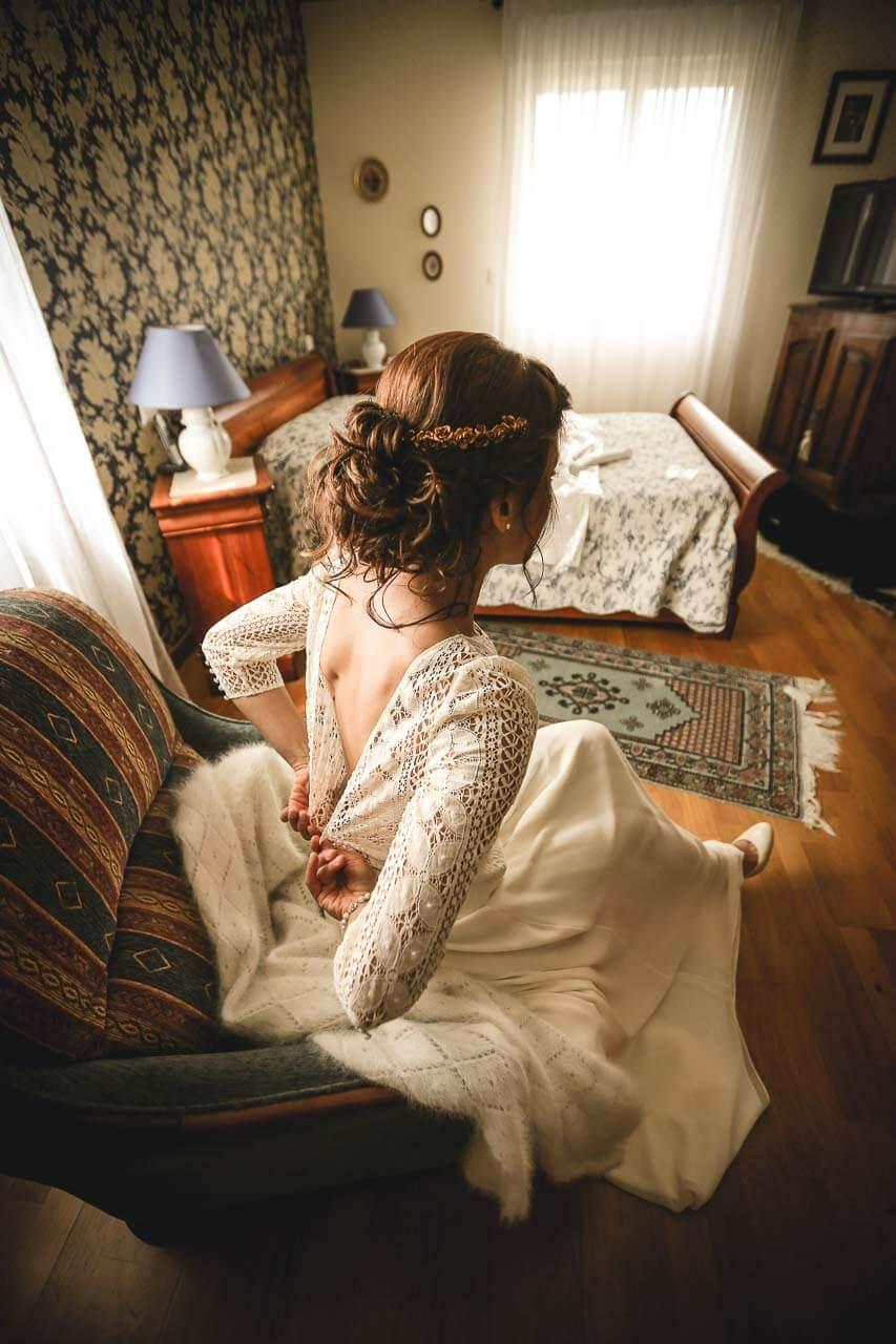 Photo de préparation au mariage Préparatifs de la mariée dans sa chambre vue de dos assis sur une chaise