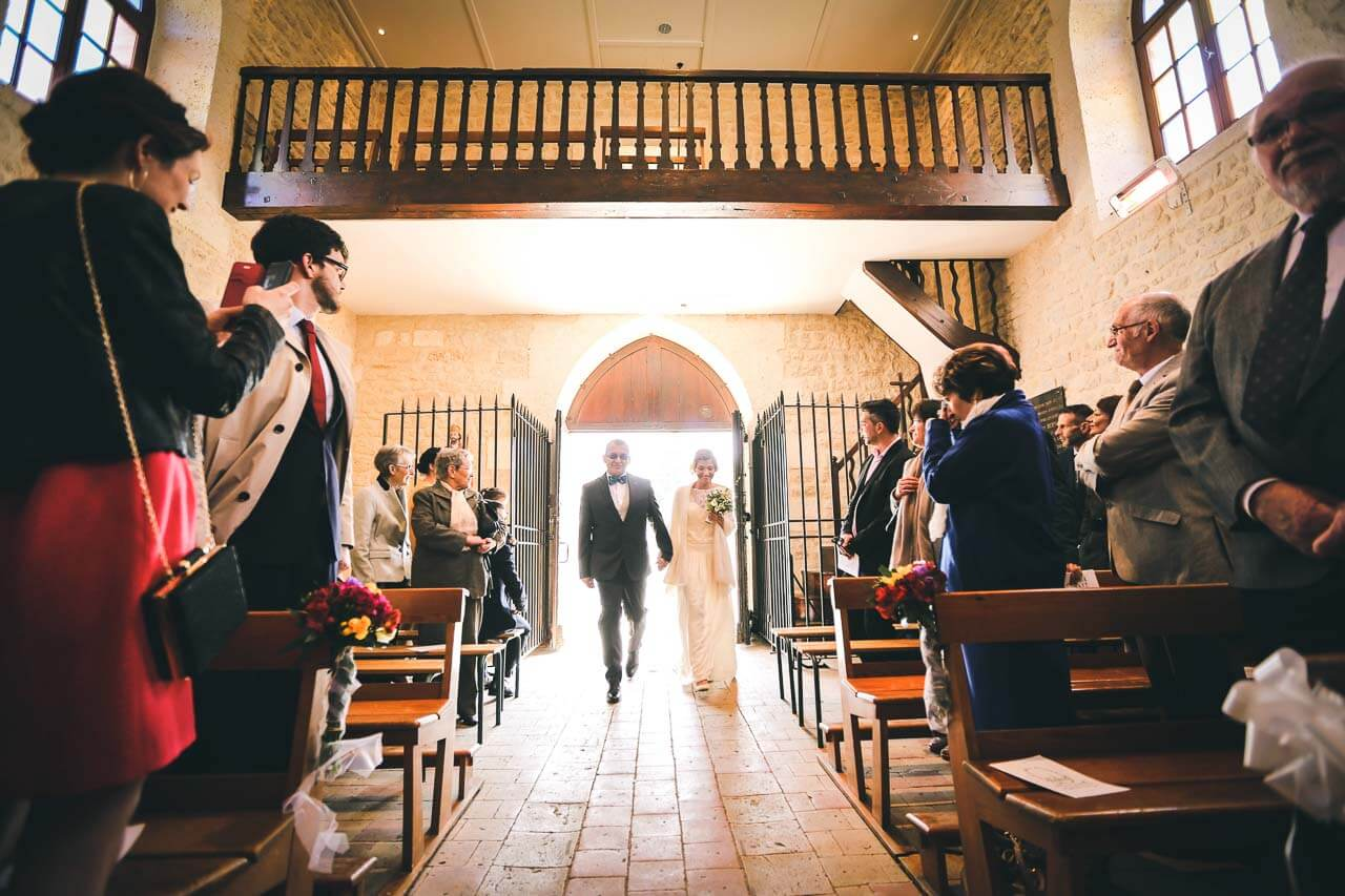 Photo de mariage à l'église Entrer dans l'église de la mariée avec son père moment d'émotion pour tous les deux