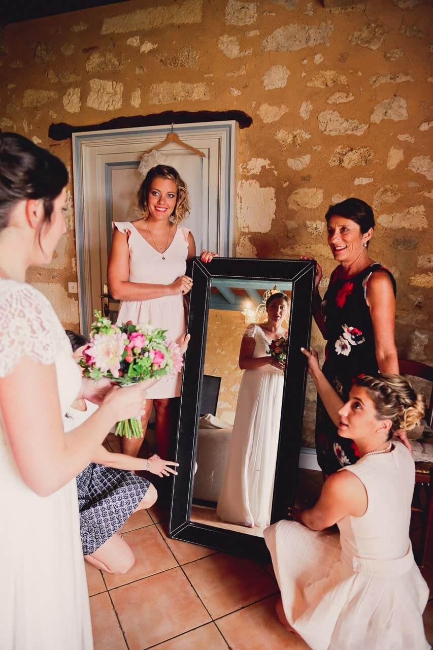 Photo de préparation au mariage Reportage de mariage préparatifs de la mariée elle se regarde dans le miroir avec tous ses amis