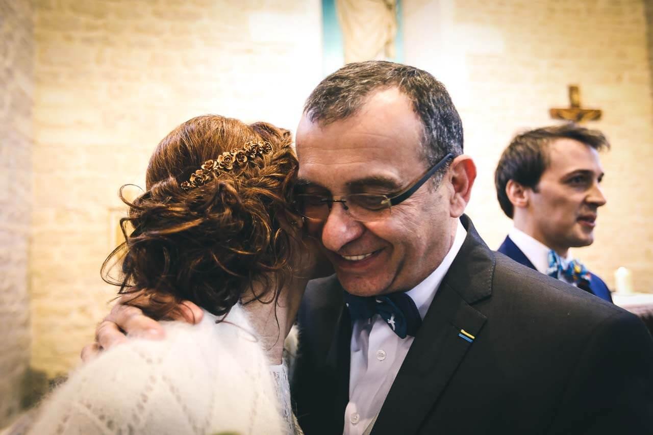 Photo avec les proches du couple Le père qui embrasse sa fille avec toutes les mentions qui peut avoir dans une photo professionnel de mariage