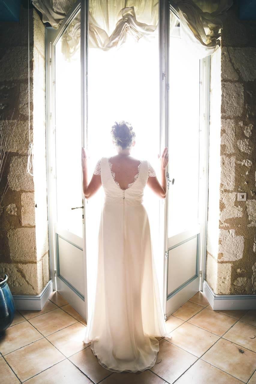 Photo de mariée en tenue Préparatifs de la mariée elle est dans la lumière extérieure de la porte en photo classe