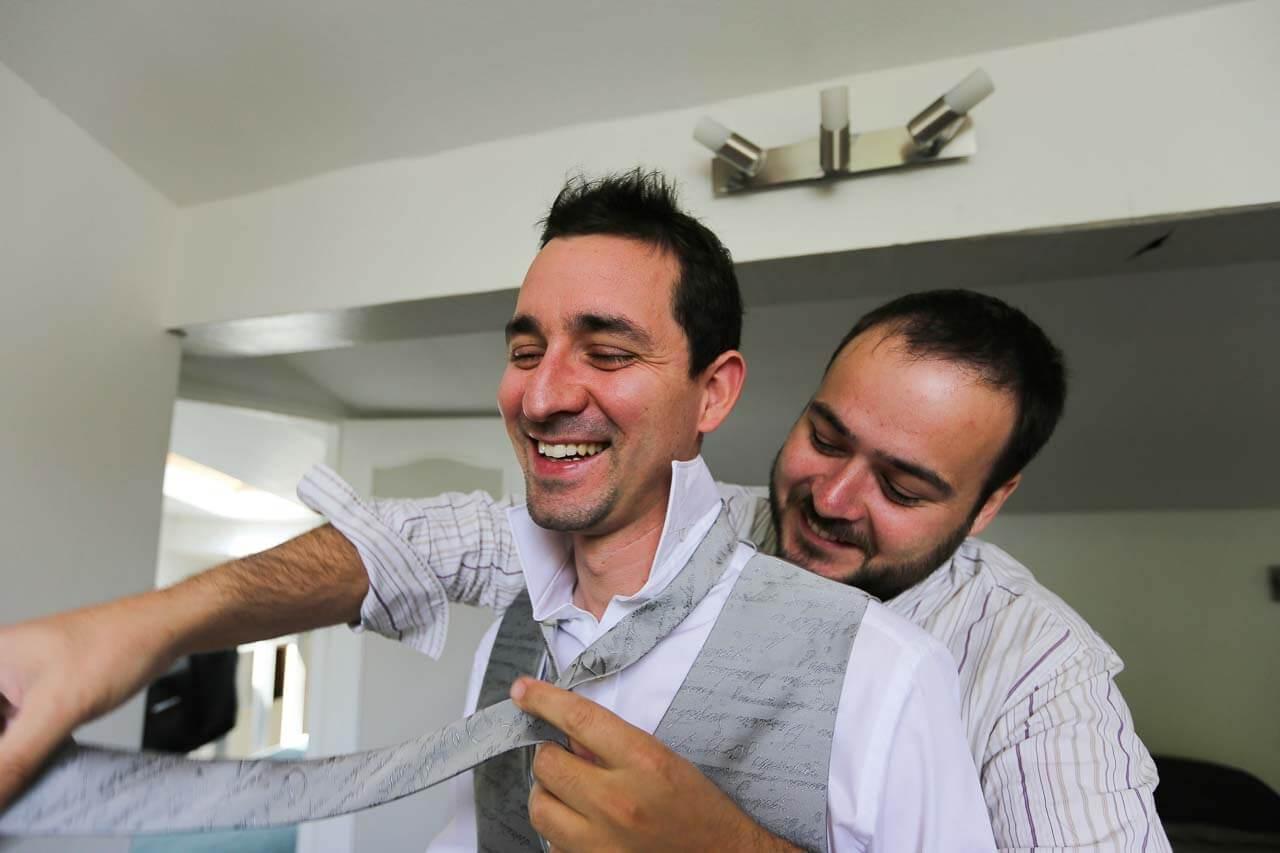 Photo de préparation au mariage Préparatifs du marié un ami derrière lui limer sa cravate le souffle chaud sur sa nuque