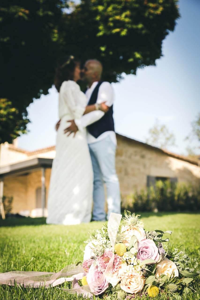 Photo de couple en tenue de mariés Portrait d'un couple qui s'embrassent avec le bouquet en premier plan