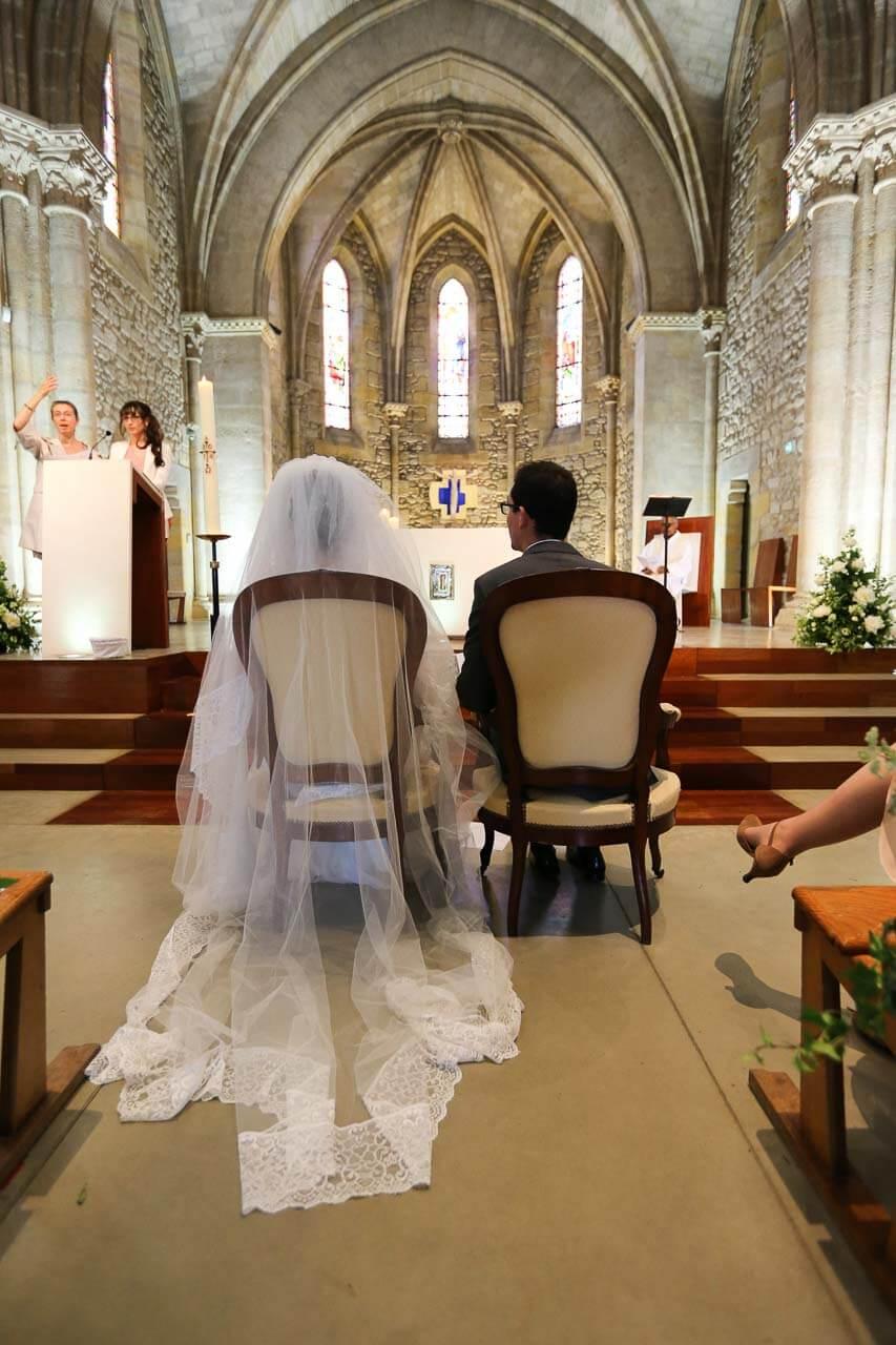 Photo de couple en tenue de mariés Prise de vue dans l'église en intérieur avec le couple vu De dos