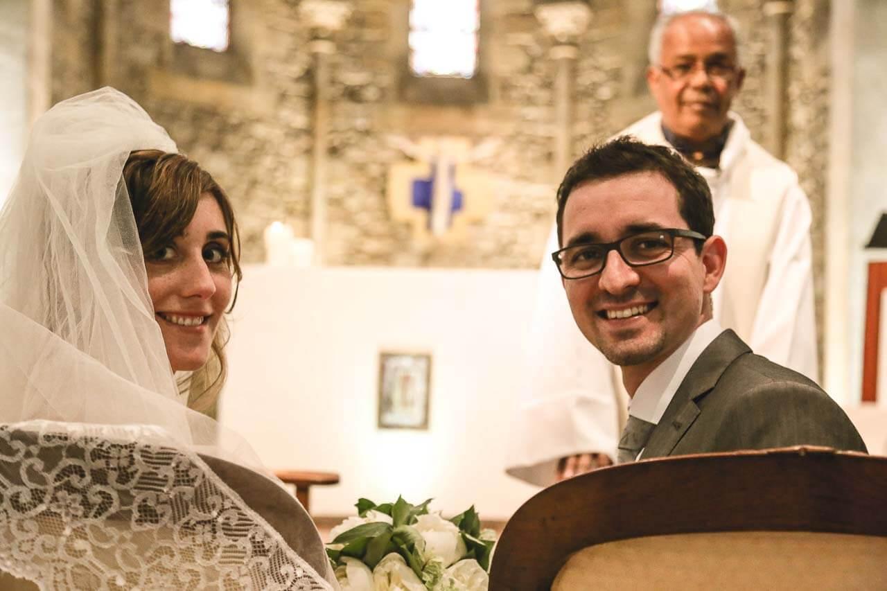 Photo de mariage à l'église Prise de vue dans l'église les mariés qui se retourne avec le prêtre en arrière plan
