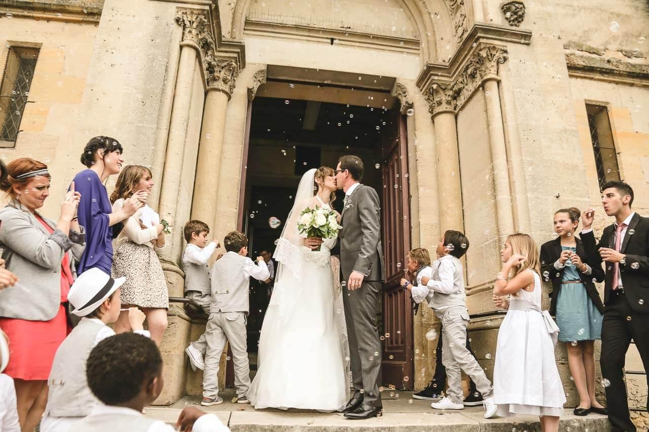 Photo de couple devant l'église Sortie d'église des mariés et les témoins et familles font des bulles ce qui donne un côté huit colique dans la photo