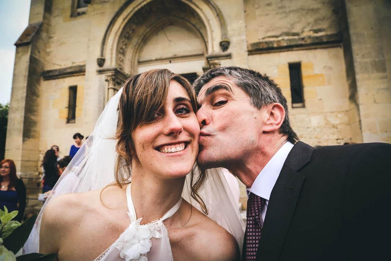 Photo de couple en tenue de mariés Le père qui embrasse sa fille à la sortie de l'église photos de joie et d'émotion