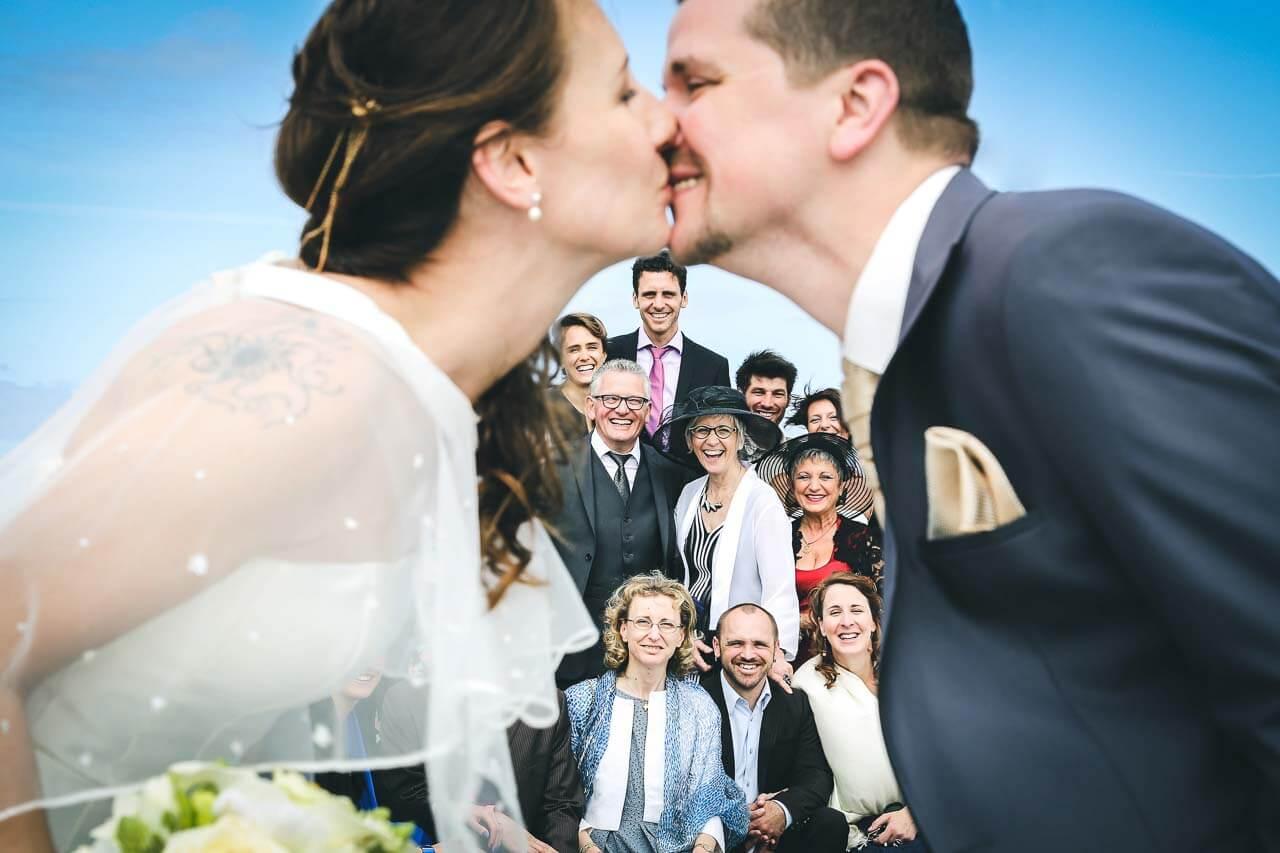 Prise de vue en extérieur à Arcachon avec la famille en arrière plan et le couple qui s'embrassent en premier plan