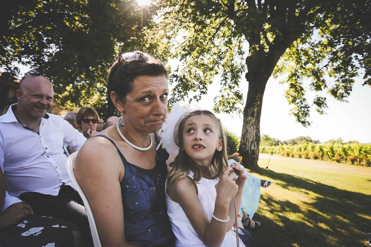 Une maman qui retient ses larmes devant l'objectif avec sa petite fille et son cousin derrière qui rigole