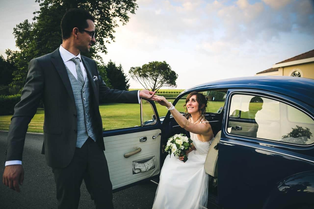 Photo de couple en tenue de mariés Photo de couple le mari est dans sa femme à sortir de la voiture une coccinelle bleue
