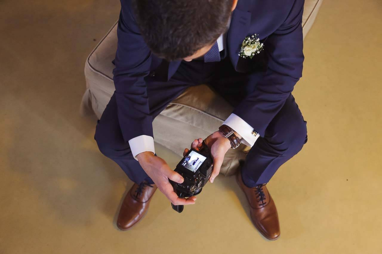 Photo du marié qui regarde des photos de son mariage
