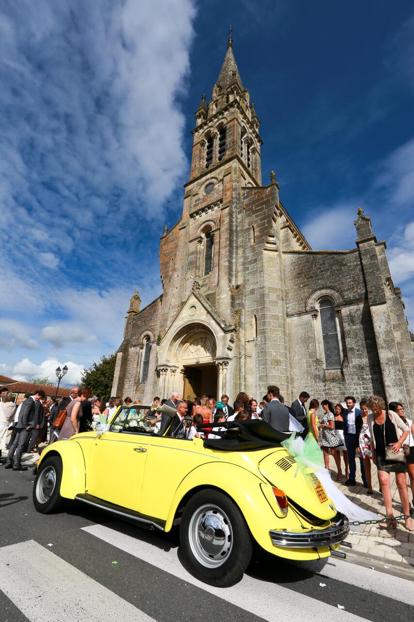 Sophie et Cédric voiture de mariée coccinelle décapotable jaune devant l'église un style différent photo journaliste Christophe Boury