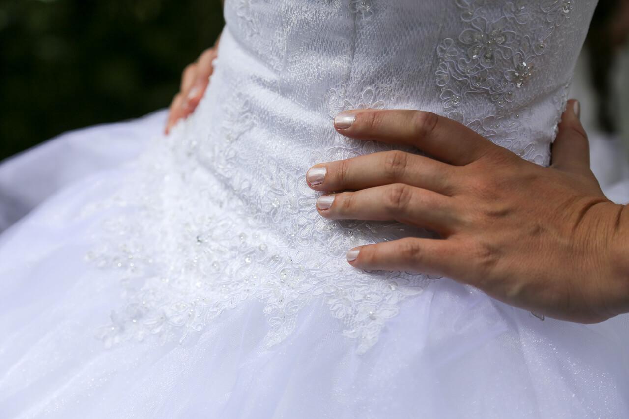 Sophie et Cédric détaille de la robe avec les mains