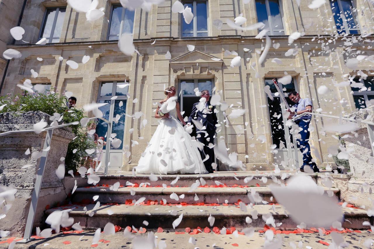 Melanie et Thomas À la porte de la mairie sous les confettisIls installation des amis