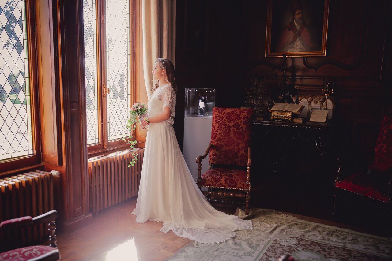 Photo de la mariée sale du Château pape clément côté mélancolique proche de la fenêtre